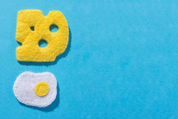 Spielzeug in form von käse und spiegelei handgemacht aus filz auf blauem hintergrund. hand nähen. speicherplatz kopieren
