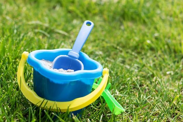 Spielzeug kinderschaufel in einem eimer auf dem gras