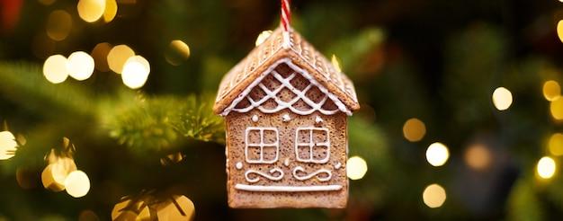 Spielzeug lebkuchenhaus hängen am weihnachtsbaum