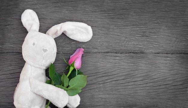 Spielzeug mit einer rose. spielzeugkaninchen mit blume auf hölzernem hintergrund