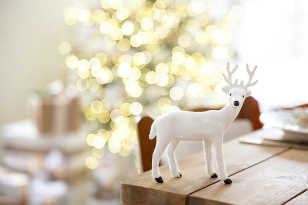 Spielzeug oder figur des hirsches auf hintergrund des unscharfen raumes und eines weihnachtsbaumes