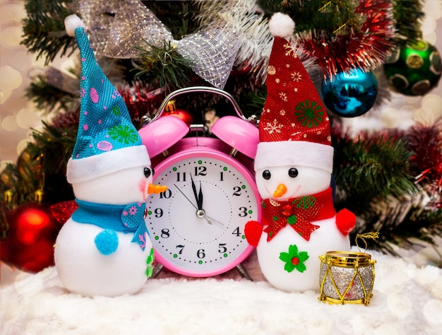 Spielzeug-schneemänner in der nähe der uhr, die das herannahen von 12 stunden, dem neuen jahr, anzeigt. schneemänner, uhr beim weihnachtsbaum_