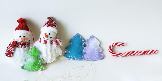Spielzeug schneemänner weihnachtsbaum auf einem hellen holzuntergrund frohe weihnachten