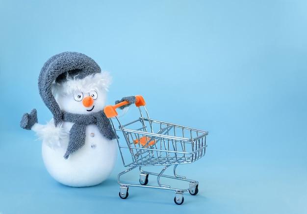 Spielzeug schneemann hält einen einkaufswagen und zeigen wie hand