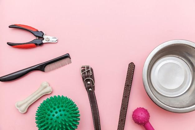 Spielzeug und zubehör für das spielen und trainieren des hundes lokalisiert auf rosa pastelltrendhintergrund