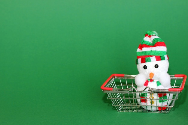 Spielzeug weihnachten schneemann ist in einem einkaufskorb aus metall aus dem supermarkt.
