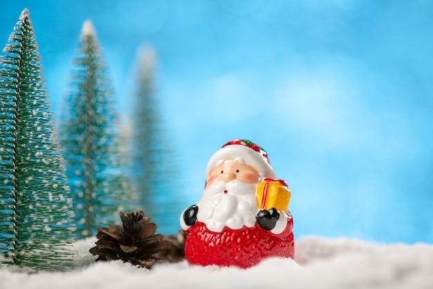 Spielzeug weihnachtsmann und weihnachtsbäume auf blauem hintergrund