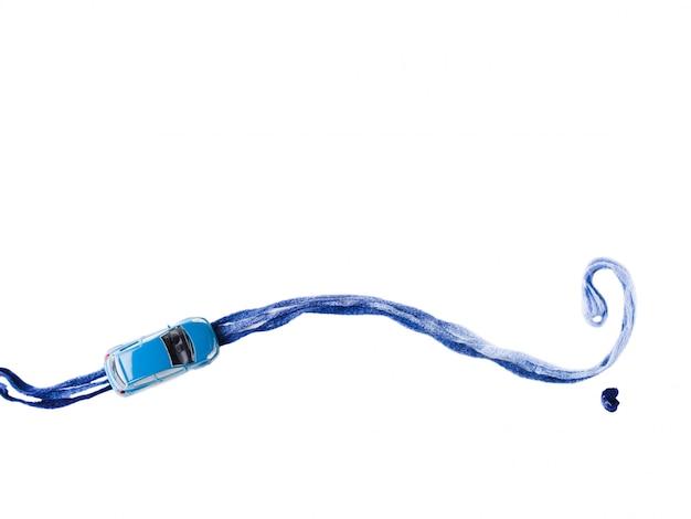Spielzeugauto auf blauer garnstraße mit fragezeichensymbol. weißgetrennt. wohin reisen? reiseziel auswahl für die zukunft