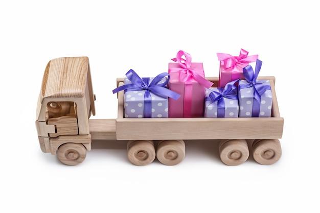 Spielzeugauto aus holz mit geschenken in kisten hinten.