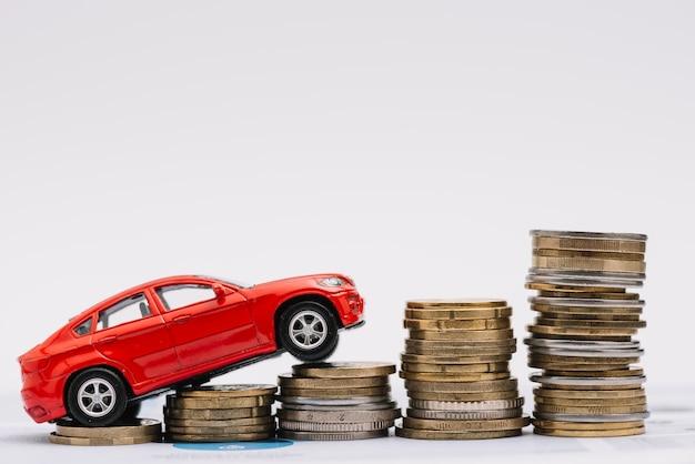 Spielzeugauto, das auf den zunehmenden stapel münzen gegen weißen hintergrund steigt