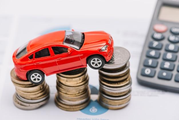 Spielzeugauto, das über dem steigenden münzenstapel balanciert