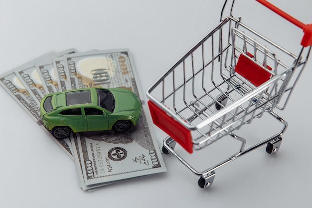 Spielzeugauto, einkaufskorb und dollarbanknoten auf einem weiß
