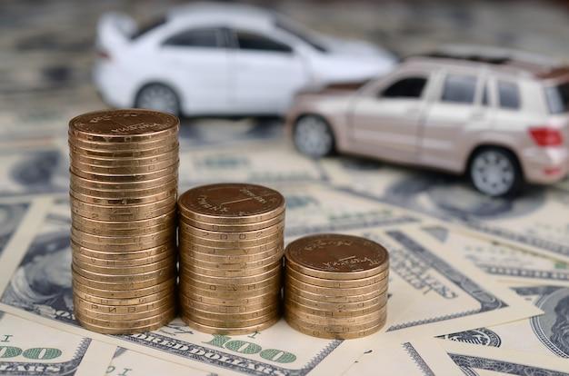 Spielzeugauto im unfall auf von 100 dollarscheinen und stapeln goldenen münzen