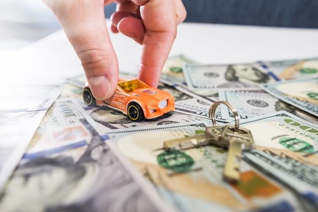 Spielzeugauto in der hand, schlüssel und geld auf dem tisch.