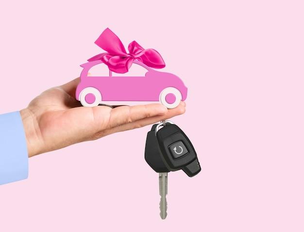 Spielzeugauto mit bogen und schlüssel auf der hand des händlers auf rosafarbenem hintergrund. autokaufkonzept