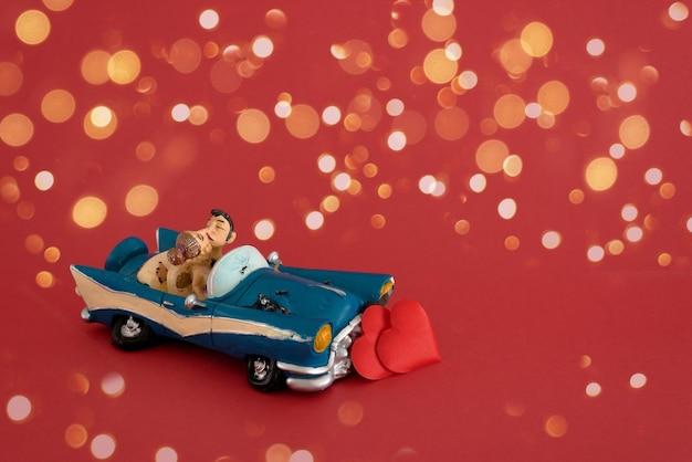 Spielzeugauto mit einem verliebten paar auf einem roten hintergrund mit hellen bokeh-girlanden, valentinstag. der mocap-copyspace.