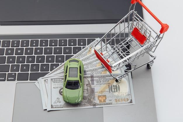 Spielzeugauto und einkaufswagen mit dollarbanknoten auf einem laptop. online-kauf auto konzept.