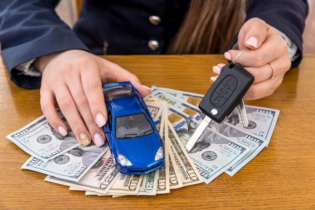 Spielzeugauto und schlüssel in den weiblichen händen auf dollarnoten