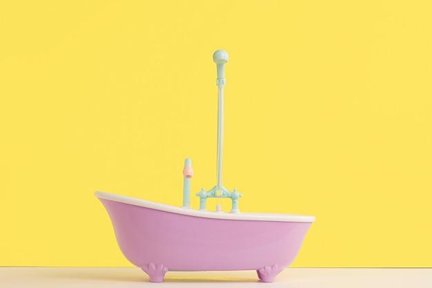 Spielzeugbadezimmer mit dusche für puppe auf gelber wand. waschen und baden von säuglingen. hygiene und pflege von kleinen kindern.
