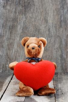 Spielzeugbärpuppe und der schmuckring mit rotem herzen.