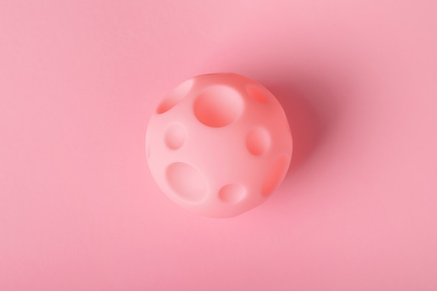 Spielzeugball mit kratern auf hellem hintergrund, das konzept der eroberung des weltraums und neuer planeten