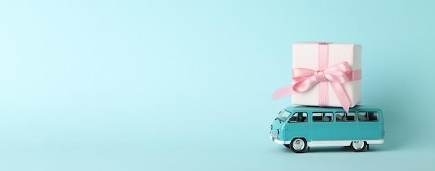 Spielzeugbus mit geschenkbox auf blauem hintergrund
