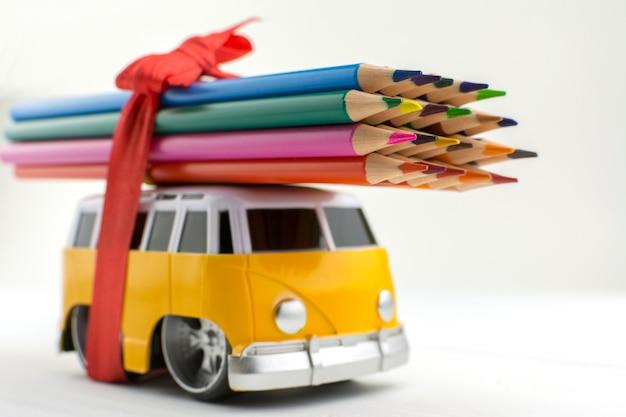 Spielzeugbus trägt eine reihe von buntstiften auf dem dach