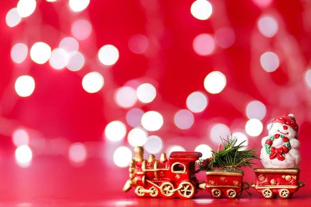 Spielzeugdampfzug mit weihnachtsbaum und schneemann auf rotem hintergrund mit bokeh. horizontales foto