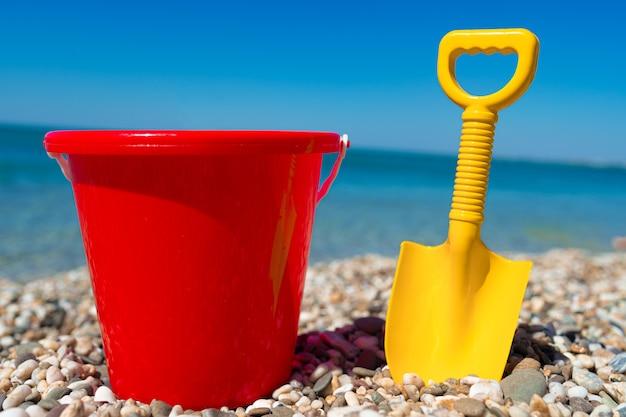 Spielzeugeimer und spaten auf den strandsteinen hautnah