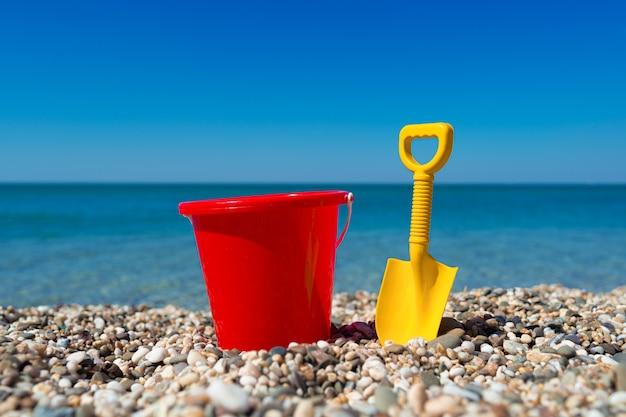 Spielzeugeimer und spaten auf den strandsteinen