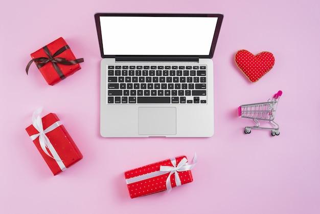 Spielzeugeinkaufslaufkatze und -herz nahe laptop und geschenken