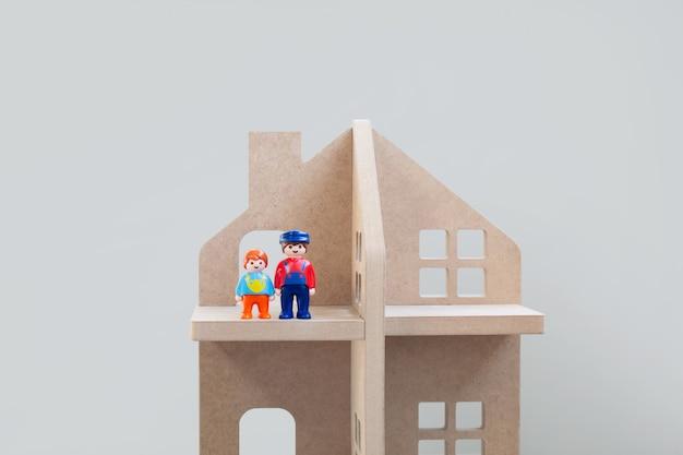 Spielzeugfiguren des vatis und des sohns, die nebeneinander in einem holzhaus stehen