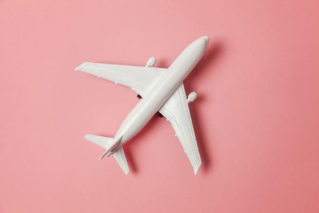 Spielzeugflugzeug auf buntem rosa hintergrund