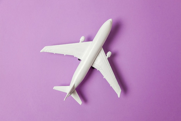 Spielzeugflugzeug auf buntem violettem purpur