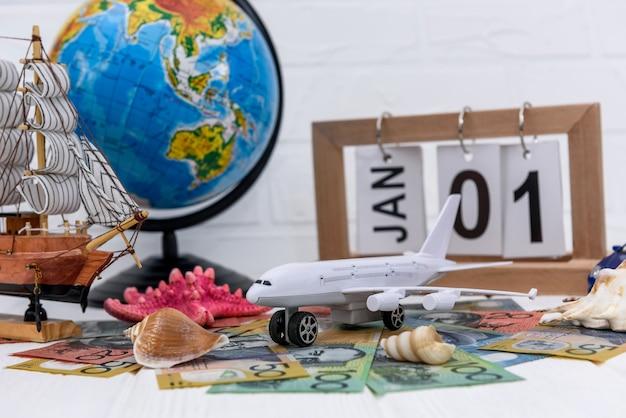 Spielzeugflugzeug mit globus und australischen dollar-banknoten