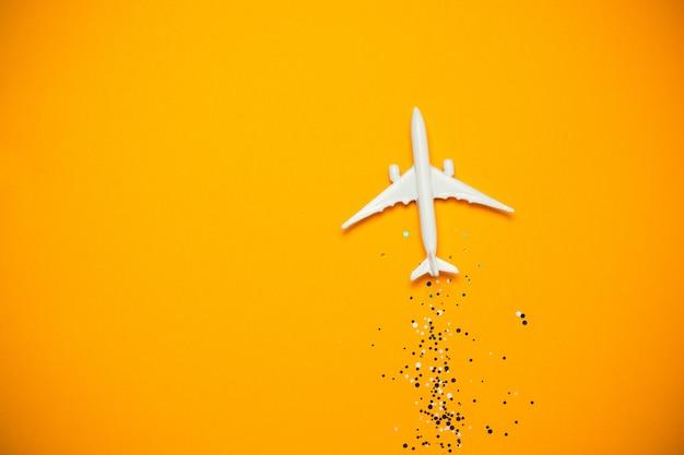 Spielzeugflugzeug mit scheinen auf gelbem hintergrund. reise