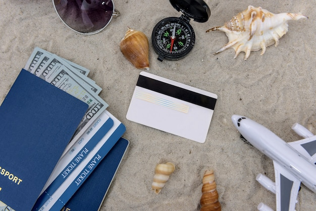 Spielzeugflugzeug, reisepass, dollarbanknoten und kreditkarte im sand