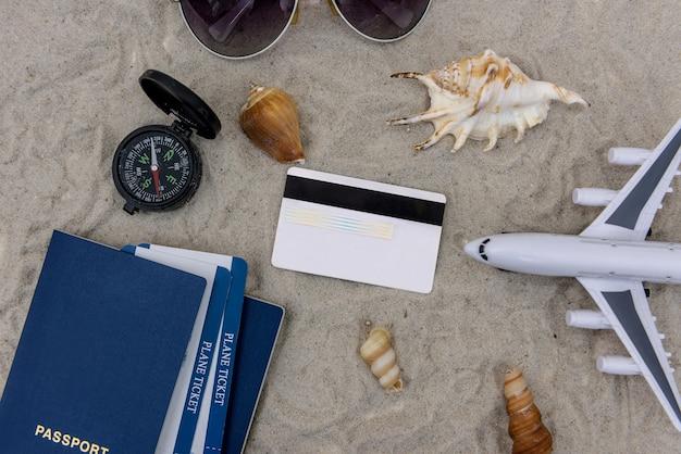 Spielzeugflugzeug, reisepass, flugtickets und kreditkarte im sand
