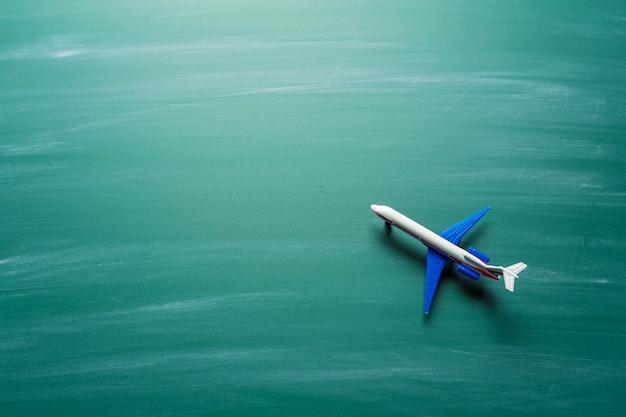 Spielzeugflugzeug über tafelhintergrund