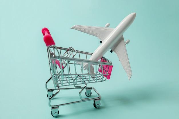 Spielzeugflugzeug und einkaufsstoßwagen auf blauem hintergrund