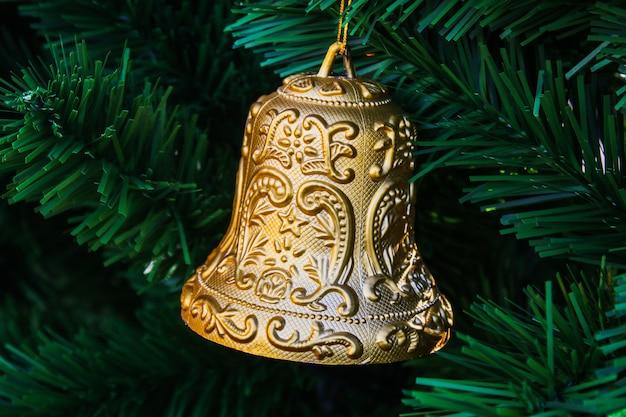 Spielzeugglocke an einem weihnachtsbaum. element des neuen jahresfeiertags