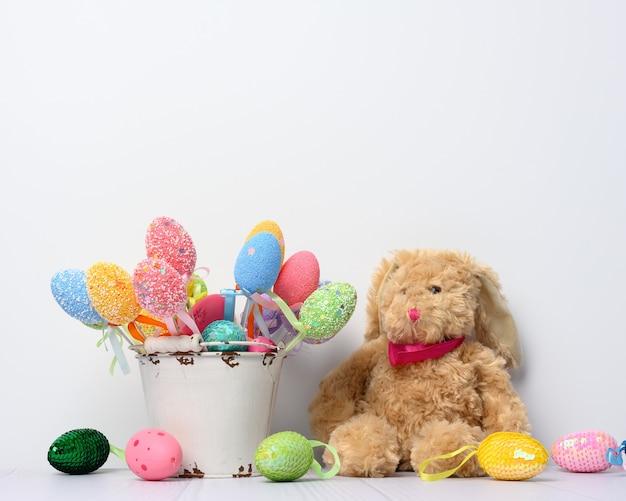 Spielzeughasen sitzen und dekorative bunte ostereier