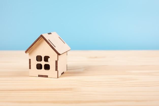 Spielzeughaus auf holztisch auf blauem baclground. haus-, versicherungs- und hypotheken-, kauf- und mietkonzept.