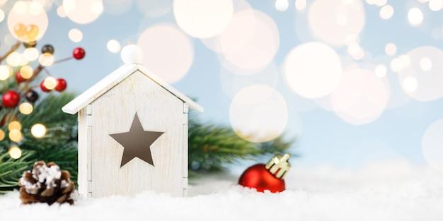 Spielzeughaus mit weihnachtsdekoration in schneeverwehung