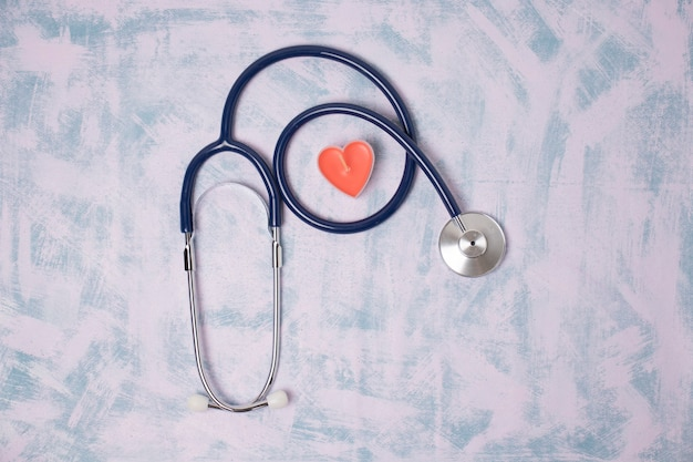 Spielzeugherz und medizinisches stethoskop auf einem blauen hintergrund, draufsicht
