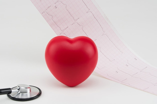 Spielzeugherz und stethoskop auf elektrokardiogrammhintergrund kardiologiepflege des herzens