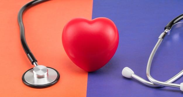 Spielzeugherz und stethoskop auf farbigem hintergrund kardiologie-pflege des herzens