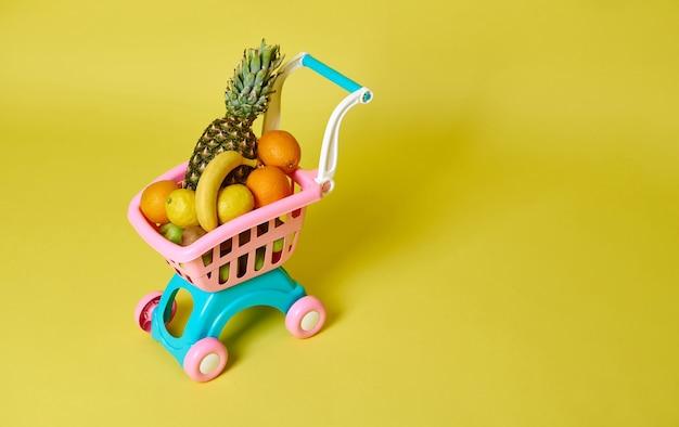 Spielzeugkinder rosa einkaufswagen voller sortierter exotischer früchte lokalisiert auf gelb mit kopienraum. high angle view