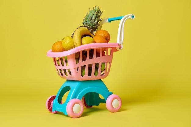 Spielzeugkinder rosa einkaufswagen voller sortierter exotischer früchte lokalisiert auf gelb mit kopienraum.