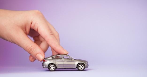 Spielzeugkinderauto in der hand der frau. kauf versicherung bank darlehen reise wohin reise reise konzept gehen.